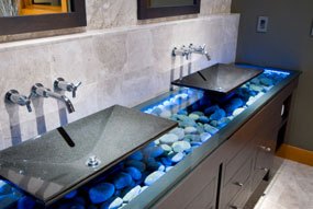 this modern asian double bathroom sink has an actual rock countertop with blue led lights covered in glass