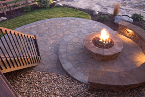 Circular Stone Fire Pit Deck With Outdoor Lighting Installed In The Seating  Areas